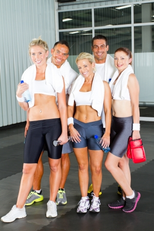 group of young people relaxing after workout in gym photo