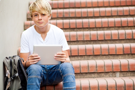 middle school: teen boy sitting on stairs and using tablet computer in school Stock Photo
