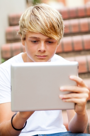 teen boy using tablet computer outdoors photo