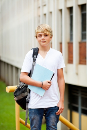 male teen high school student in front of school building photo