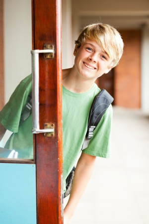 cute high school boy behind classroom door photo