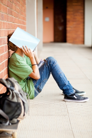 sad boy: frustrated high school boy using book cover his face in school passage Stock Photo