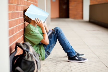 high school: tired high school student using book cover his face