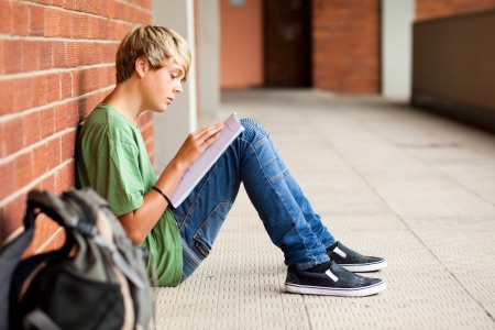 student reading: teen high school student reading book in school passage Stock Photo