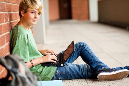 ni�o con mochila: estudiante adolescente con ordenador port�til en el pasaje de la escuela