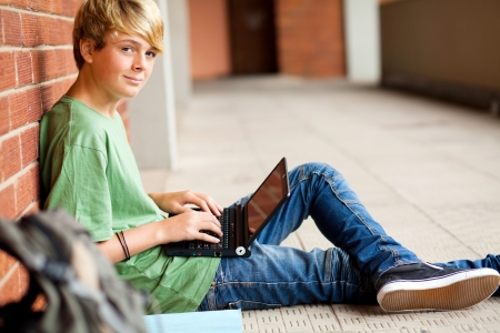 teen student using laptop in school passage