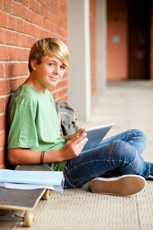 male high school teen student using tablet computer in school photo