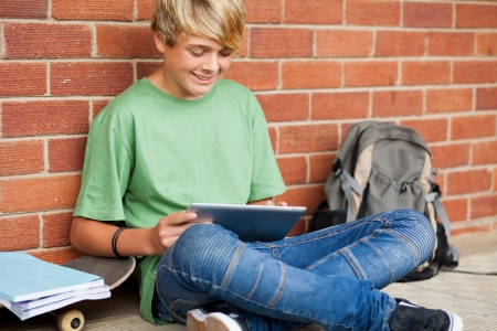 teen boy using tablet computer in school photo