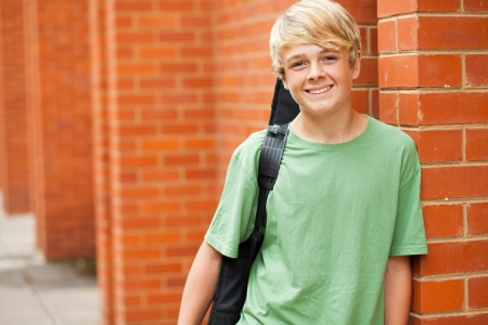 happy male teen musician carrying his guitar photo
