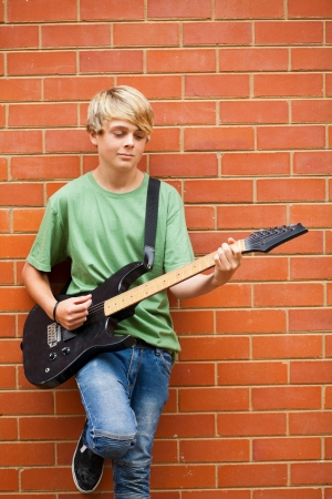 teen boy playing guitar outdoors Stock Photo - 13738900