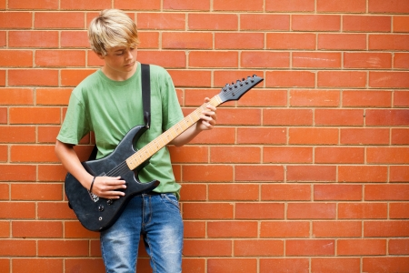 teen boy playing guitar outdoors photo