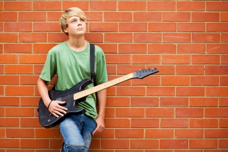 teen boy with guitar daydreaming photo