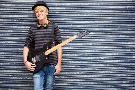 teen musician portrait with guitar outdoors photo
