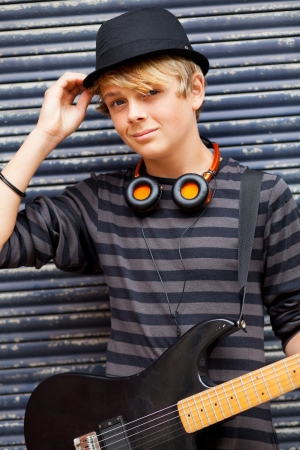 male teen musician portrait outdoors with guitar photo