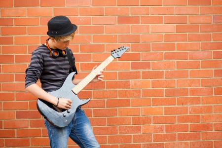 teen boy playing guitar outdoors Stock Photo - 13738652