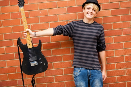 cute teen musician holding guitar photo
