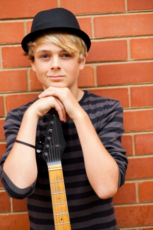 handsome teen musician portrait with guitar photo
