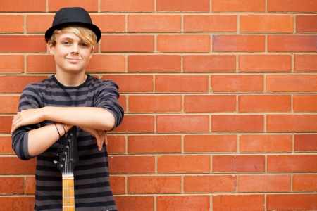 handsome teen boy with guitar outdoors photo