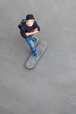 happy teen skateboarder standing on skateboard and looking up photo