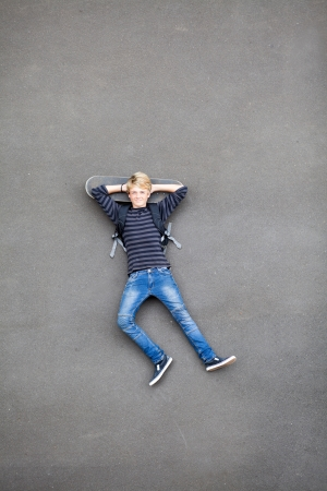 overhead view of teen skateboarder lying on his skateboard photo