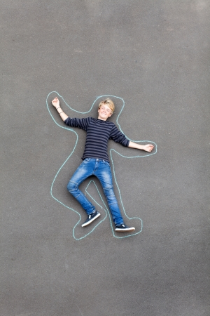 ground floor: playful teen boy lying on ground with lines drawn around him Stock Photo