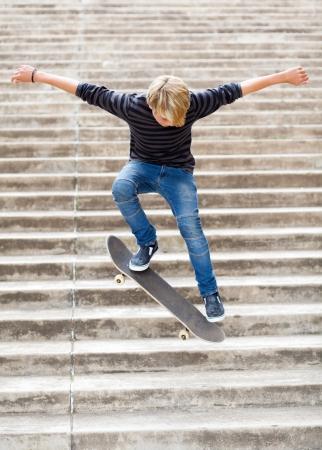 niño en patines: adolescente niño de skate en las escaleras