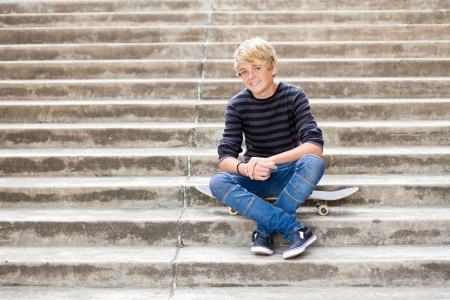 handsome teen boy sitting on skateboard photo