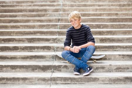 boy skater: handsome teen boy sitting on skateboard
