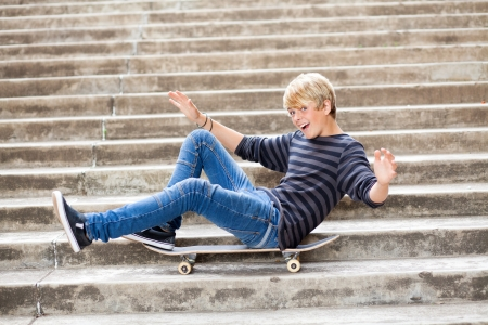 playful teen boy sitting on skateboard photo