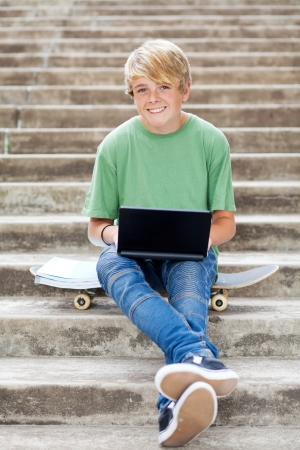 cute teen boy with laptop outdoors Stock Photo - 13737601