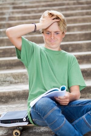 teen boy looking frustrated while reading a book photo