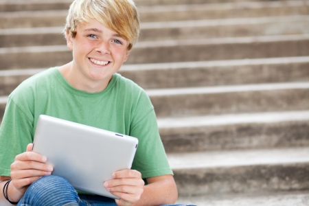 young teen boy using tablet computer photo