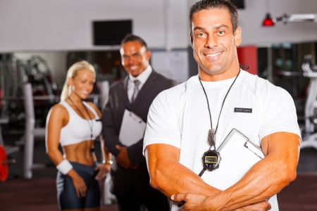 fitness trainer: muscular senior gym trainer portrait with colleagues in background Stock Photo