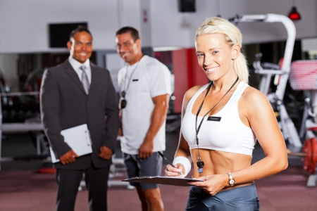 happy female gym trainer portrait with colleagues in background photo
