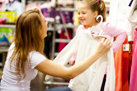 clothing store: mother and daughter shopping for clothes