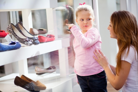 mother and daughter shopping, daughter pointing at shoes she likes photo