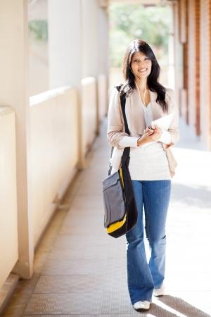 attractive female college student walking down school corridor photo