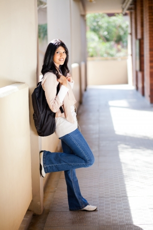 attractive female student standing by university corridor photo