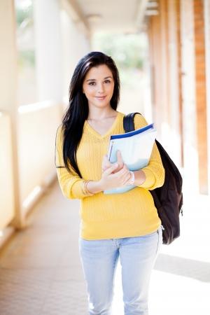 uni: pretty female university student walking down school corridor