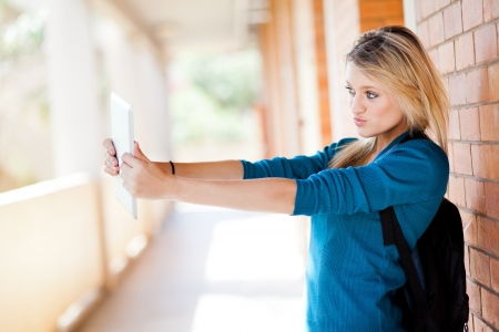 cute female college student using tablet computer taking self portrait on campus photo