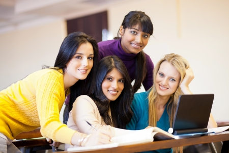 group of young female college students using laptop in classroom photo