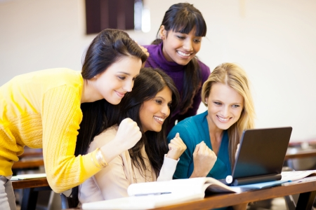 group of female college students cheering a game on laptop photo