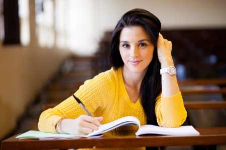 student desk: beautiful female college student sitting in classroom