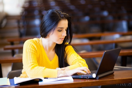 attraente studentessa universitaria con laptop in aula Archivio Fotografico