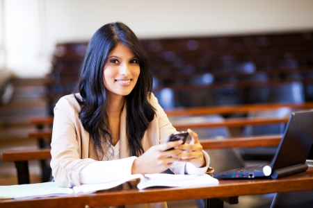 beautiful college student in lecture hall with mobile phone sending sms photo