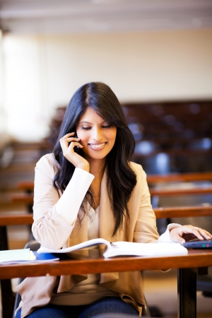 female university student talking on cell phone in classroom photo