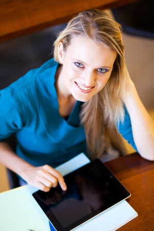 attractive young female university student using tablet computer photo