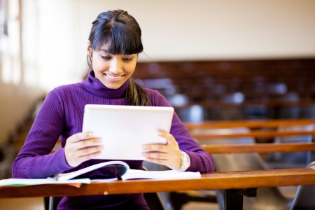 happy female indian college student using tablet computer in classroom photo