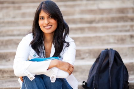 indian college student: attractive female college student sitting outdoors Stock Photo