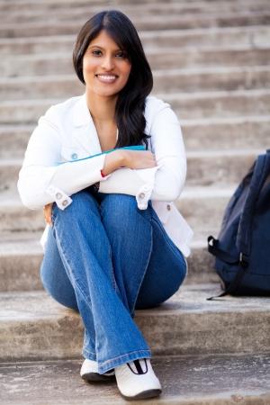 beautiful young female university student sitting outdoors photo